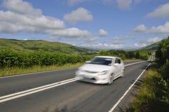 White car on Scottish road Stock Photo
