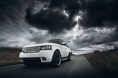 White car speed driving on road at dramatic clouds daytime Stock Images