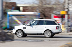 White car at speed. White car at high speed going down the street. Panning Stock Photo