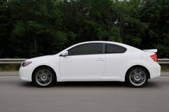 White car speeding on highway. A white Scion tC speeding on the highway Royalty Free Stock Photo