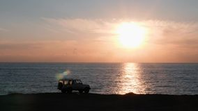 White car standing on cliff against pink sunset. Cliff with car standing on it and amazing view of ocean. Vehicle standing near e. Dge of cliff surrounded by stock footage