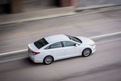 White car on street. A white car on the street with a motion blur Royalty Free Stock Images