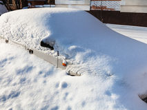 White car under snowdrift in parking lot Royalty Free Stock Images