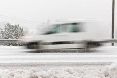 White car, van driving fast on the road in winter landscape, with snowy weather. Motion blur Royalty Free Stock Image