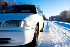 White car on winter snowy country road royalty free stock photography