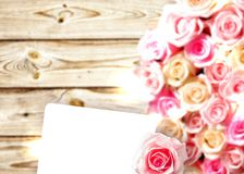 White card on the background of roses and wood Royalty Free Stock Photo