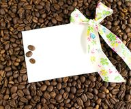 Coffee beans. White card and bow on a background of coffee beans. White card, bow and background of coffee beans Stock Photography