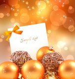 White card with Christmas balls. On a bright Golden background there are Christmas balls and white card with an orange bow. There is plenty of space for text or royalty free stock photos