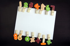White card with clothespin. White blank card surrounded by clothespin in black wooden background Stock Photography