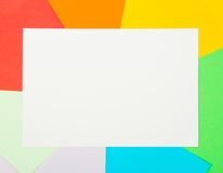 White card on color sheets of paper Royalty Free Stock Photography