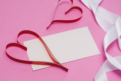 White card with with copy space, red homemade paper hearts and a white ribbon on a pink background. Symbol of Valentine`s Day stock photos
