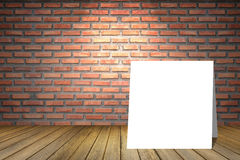 White card among empty room of old red brick wall.Perspective brown wooden floor.spot light from top.for display present product. White card among empty room of Royalty Free Stock Photos