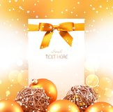 White card with Golden Christmas balls. On a bright Golden background there are Christmas balls and white card with a gold bow. There is plenty of space for royalty free stock photography
