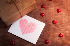 White card with a heart on wooden background. Valentine's day. White card with a heart on wooden background Stock Photography