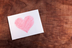 White card with a heart on wooden background. Valentine's day. White card with a heart on wooden background Royalty Free Stock Photos