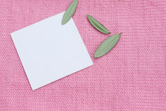 White card on a knitted pink wool green leaves Stock Photo