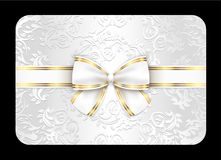White card with ornament and white ribbon Royalty Free Stock Photo