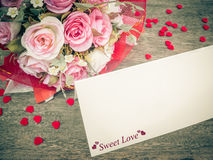 White card and pink rose bouquet on wood Stock Images