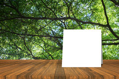 White card put on Wooden desk or wooden floor on green bokeh background.use for present or mock up your product.clipping path Stock Photos