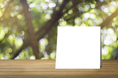 White card put on Wooden desk or wooden floor on green bokeh background.use for present or mock up your product.clipping path Stock Photography