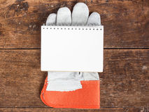 White card in  safety glove on wooden Royalty Free Stock Photos
