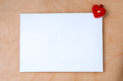 White card with a small red heart on wooden background. Royalty Free Stock Image
