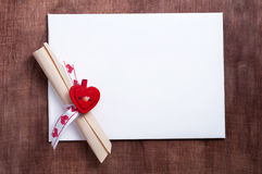White card with a small red heart on wooden background. Valentine's day. White card with a small red heart on wooden background.A scroll of paper with wishes Stock Image