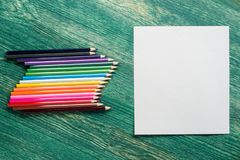 White card for text or paintings with colourful pencils on wooden background. Art mock up for your text or graphic. White card for text or paintings with stock photography