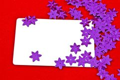 White card and violet stars on red background Stock Photos