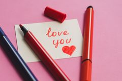 White card with the word `love you` and colored markers on a pink background royalty free stock image