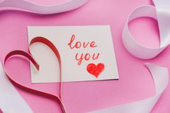 White card with the words `love you`, a red homemade paper heart and a white ribbon on a pink background. Symbol of Valentine`s Da royalty free stock images