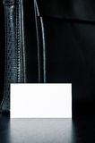 White card for writing with black leather bag on the table Royalty Free Stock Photos