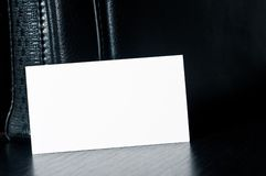 White card for writing with black leather bag on the table Stock Photo