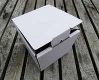 Cardboard mailing box on wooden deck. White cardboard mailing box on wooden deck floor Royalty Free Stock Images
