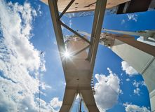 White cargo crane in the harbour, photographed from below in the direction of the sun through the supports, abstract impression, royalty free stock photography