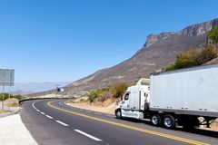 White cargo truck on the road between rocky and arid mountains at noon stock photos