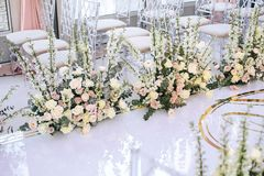The white carpet for the wedding ceremony is decorated with flower compositions of roses, buttercup and bells with transparent cha royalty free stock photo