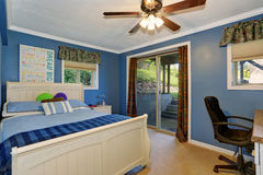 White carved wooden double bed in blue bedroom Stock Image