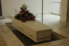 White casket with funeral flowers. White coffin with funeral flowers in a crematorium stock photo