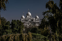 White castle. A shot of a meajestic white castle slightly hidden by trees around it. The shot was taken in Ajmer, India Stock Photo
