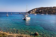 White catamaran docked in ancient bay of Knidos against blue sky royalty free stock image