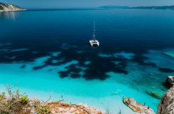 White catamaran yacht at anchor in calm clear azure water lagoon. Unrecognizable tourists relax and leisure on the royalty free stock photos
