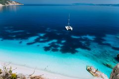 White catamaran yacht drift on clear azure water surface in calm blue lagoon with transparent water and dark pattern on royalty free stock image