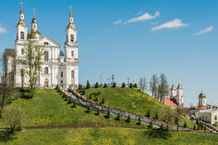White cathedral with domes is located on the green mountain, on the sides of the stairs are lanterns and coniferous trees grow. Near the mountain there are Stock Photo