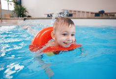 White Caucasian child in swimming pool. Preschool boy training to float with red circle ring in water Royalty Free Stock Photo