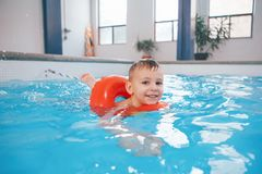 White Caucasian child in swimming pool. Preschool boy  training to float with red circle ring in water. Portrait of happy white Caucasian child in swimming pool Royalty Free Stock Photo