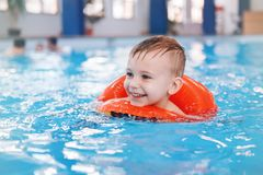 White Caucasian child in swimming pool. Preschool boy training to float with red circle ring in water Royalty Free Stock Image