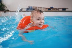 White Caucasian child in swimming pool. Preschool boy  training to float with red circle ring in water. Portrait of white Caucasian child in swimming pool Royalty Free Stock Images