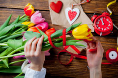 White caucasian female hands wrapping tulips near things for dec royalty free stock image