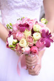 White Caucasian female holding a mixed, colorful bouquet. Vertical shot of a young bride holding a purple hues wedding bouquet. Wedding ideas for floral royalty free stock photos